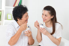 Asian women eating yogurt. Eating yoghurt . Happy Asian family eating yogurt at home. Beautiful senior mother and adult daughter, healthcare concept Royalty Free Stock Photography