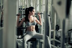 Asian women exercising with a lat pulldown machine to play the arms and shoulder muscles in the gym. Exercise in the gym. Asian woman exercising with a lat stock photos