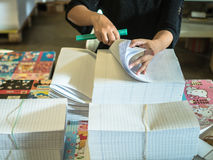 Asian women fold a piece of paper to ready to make a books. In book factory royalty free stock photo