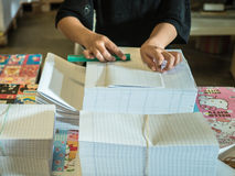 Asian women fold a piece of paper to ready to make a books. Asian women fold a piece of paper to ready to make a books in book factory royalty free stock image