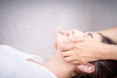 Women is getting face massage side view with cement wall copy space Royalty Free Stock Images