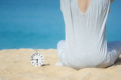 Asian women in a gray dress sitting beside the white alarm clock placed on the sand. Blue sea and sky as a background. Concept for royalty free stock photos