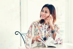 Asian women have a sense. Asian woman have a sense of comfort when phoning in the shade Stock Image
