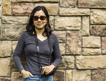 Asian women holding camera against stone wall Royalty Free Stock Photos