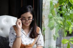 Asian women are holding glasses and smiling at a coffee shop on royalty free stock photo