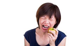 Asian women with intense toothache pain after biting apple Royalty Free Stock Images