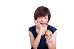 Asian women with intense toothache pain after biting apple Stock Photography