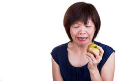 Asian women with intense toothache pain after biting apple Stock Photos