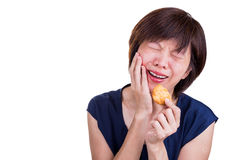 Asian women with intense toothache pain after biting cookie Royalty Free Stock Photography