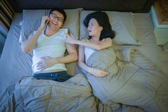 Asian women jealous of her boyfriend talking on the phone on bed stock image