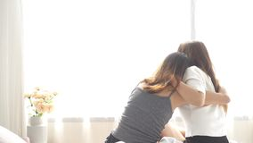 Asian women lesbian happy couple waking up in morning. Asian girls sitting on bed stretching in cozy bedroom at home. stock video footage