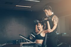 Asian woman lifting dunbbell while man coach assisting holding s. Asian women lifting dunbbell while men coach assisting holding suspensory elbow her at gym Royalty Free Stock Photos
