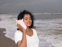 Asian women listening to the shell. Asian women of indian origin listening to the shell Stock Photo