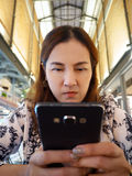 Asian women look at mobile phone and furious. Royalty Free Stock Images