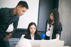 Asian women and men engineers discussing business project and sm. Iling indoors Stock Photography