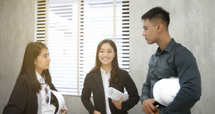 Asian women and men engineers discussing business project and sm. Iling indoors Royalty Free Stock Photos