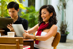 Asian people in cafe with computer. Asian women and men are sitting in a bar or cafe outdoor and are surfing the internet with a tablet computer royalty free stock images