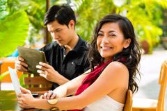 Asian people in cafe with computer. Asian women and men are sitting in a bar or cafe outdoor and are surfing the internet with a tablet computer stock photo