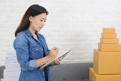 Asian women note orders with box at home business concept. Asian woman note orders with box at home business concept royalty free stock photography