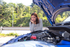 Asian women opened the hood and looking at broken down car Royalty Free Stock Photos