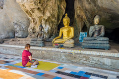 Asian women pilgrim worships the Buddha statues at cave of Wat Tham Khao Wong. Wat Tham Khao Wong is a Buddhist temple area in Uthai Thani, Thailand, Asia Royalty Free Stock Image
