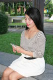 Asian women playing phone in the park. Stock Photos