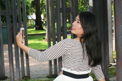 Asian women playing phone in the park. Asian woman playing phone in the park. using the phone with emotions Royalty Free Stock Photos