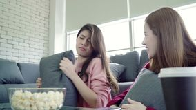 Asian women playing pillow fight and eating popcorn in living room at home, group of roommate friend enjoy funny moment. Asian women playing pillow fight and stock video footage