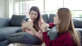 Asian women playing pillow fight and eating popcorn in living room at home, group of roommate friend enjoy funny moment. stock video footage