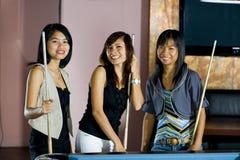 Asian women playing pool Royalty Free Stock Photo