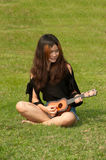 Asian women playing Ukulele in park outdoor . Stock Photo