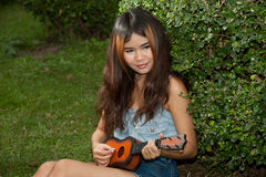 Asian women playing Ukulele in park outdoor . Royalty Free Stock Photo