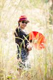 Asian women portrait with red umbrella. Portrait of Asian woman with red hat red umbrella in nature park garden white grass background Royalty Free Stock Photography