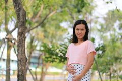 Asian women are pregnant for about twelve weeks. Asian woman are pregnant for about twelve weeks to enjoy and happy in the garden Royalty Free Stock Photography