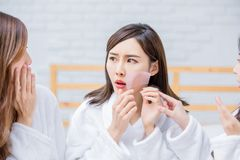 Asian women with oily skin. Asian women put the oil absorbing paper on her face and feel bad stock image