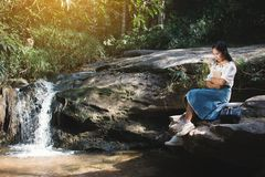 Asian women reading a book sitting on the rock near waterfall in forest background Stock Photos