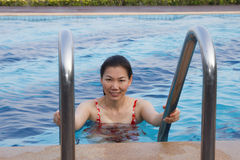 Asian women relaxing in pool on vacation. Royalty Free Stock Photos