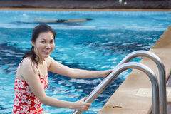 Asian women relaxing in pool on vacation. Royalty Free Stock Images