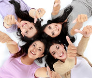 Asian women relaxing smiling lying on the floor. Four young attractive asian women relaxing smiling lying on the floor showing thumbs up Royalty Free Stock Image