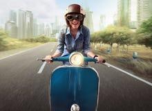Asian women riding a blue scooter. Asian woman riding a blue scooter along a city street Stock Image