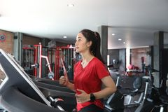Asian women running sport shoes at the gym while a young caucasi Stock Photo