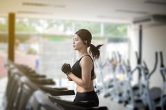 Asian women running sport shoes at the gym while a young caucasi. Asian woman running sport shoes at the gym while a young caucasian woman is having jogging on Stock Image