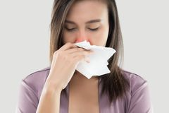 Hay fever. Asian Women In Satin Nightwear Feeling Unwell And Sneeze Against White Background, Dust Allergies, Flu, People Caught Cold And Allergy Royalty Free Stock Image