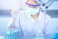 Asian women scientist with test tube making research in clinical laboratory.Science, chemistry, technology, biology and people con. Professional distinguished royalty free stock image