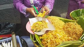 Asian women serve noodles with hands in street food Jakarta stock footage