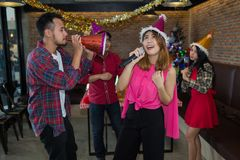 Asian woman singer in santa claus hat with a microphone singing and dancing in Christmas party and friend in restaurant. royalty free stock photo