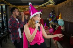 Asian woman singer in santa claus hat with a microphone singing and dancing in Christmas party and friend in restaurant. stock image