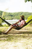 Asian women sit and relaxing on furniture Hammock hanging betwee Stock Photo