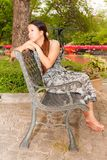 Asian women sitting on bench in park from side Royalty Free Stock Images