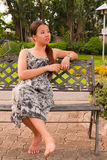 Asian Women Sitting On Bench Faced Left Stock Photo